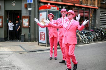 Offbeat performers in pink suits