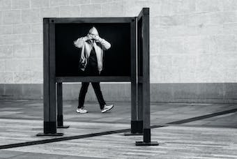 Artistic image of a person walking behind a frame